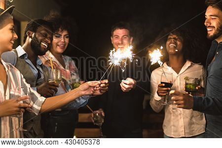 Happy Young Friends Having Fun With Sparklers Fireworks And Drinking Cocktails On House Patio Party