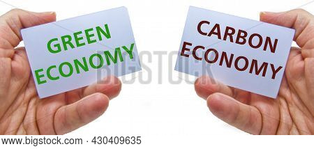Man Hands Holding Cardstocks With The Words Green Economy And Carbon Economy. Concept For Ecology, R