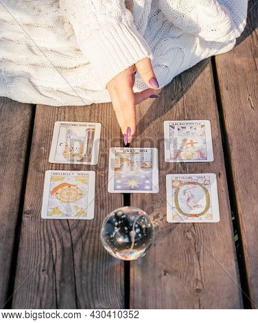 Woman's Hand With Purple Nails Points To Five Tarot Cards Spread Out On Wooden Surface Next To Cryst