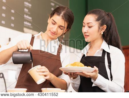 Half-body Angle Of Caucasian And Asian Barista Women Preparing Takeaway Hot Coffee And Bread For Cus