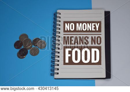 A Phrase Of No Money Means No Food Written On A Notebook With Coins Isolated In Blue And White Backg