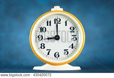 Yellow Alarm Clock Shows Time 21 O'clock On Turquoise Isolated Background