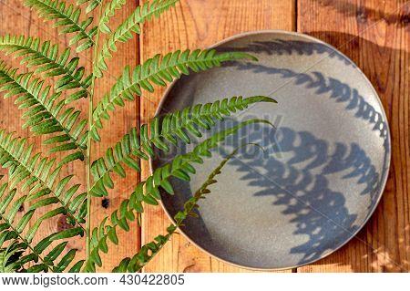 Green Fern Leaf With Hard Deep Shadows On A Wooden Background. Clay Plate With Fern Shadows.