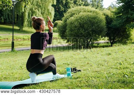 Young Fit Woman In Sportswear Performs Yoga Asana On Fitness Mat, Balance And Outdoor Wellness Worko