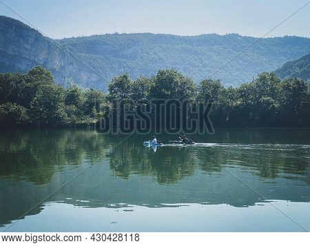 Two peoples kayaking on the coiselet lake, Jura, France