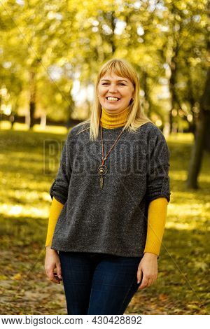 Defocus Smiling Blond 40s Woman Standing In Yellow Autumn Park. Happy Beautiful Lady. Women Wearing