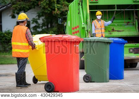 Garbage Men Working Together On Emptying Dustbins For Trash Removal With Truck Loading Waste And Tra