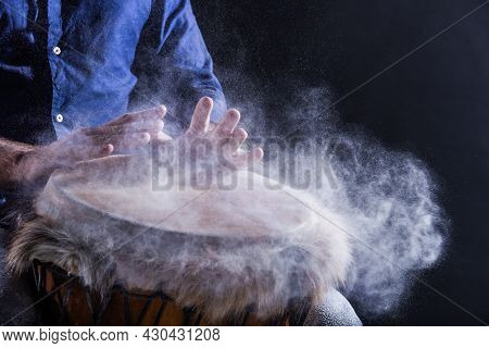 Man Is Playing On Djembe Drum, Covered With Talcum Powder. Flour Splashes On Dark Background. Summer
