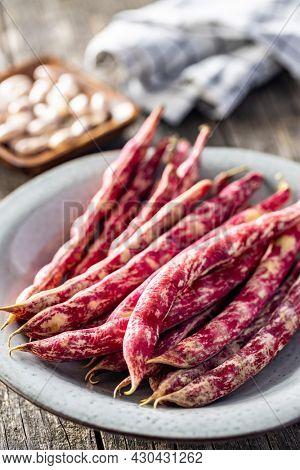 Cranberry beans. Borlotti beans. Beans pods on a plate.