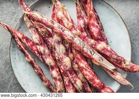 Cranberry beans. Borlotti beans. Beans pods on plate. Top view.