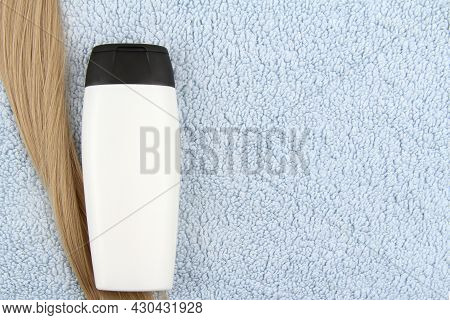 A Mock-up Of A White Bottle Of Cosmetic Shampoo And A Strand Of Blonde Hair Lies On A Blue Towel.hai