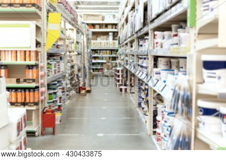 Blurred Aisle And Shelves With Building And Finishing Materials In Hardware Store. View Of Hypermark