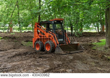 Skid Steer Loader Clearing The Site In Public Park Moving Soil And Performing Landscaping Works For