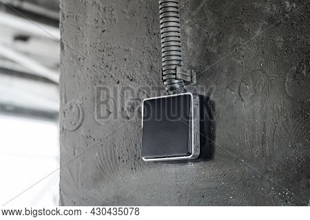 Industrial Light Switch Close-up. Black Button On Grey Surface.