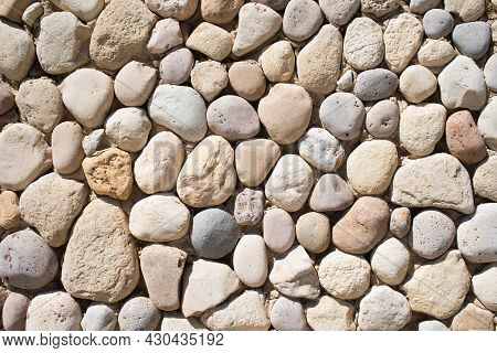 Stone Wall Made Of Stones With Different Shapes And Tones. Traditional Wall