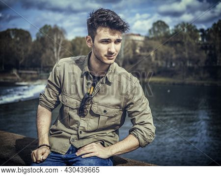 Three-quarter Length Of Young Man Standing Beside Picturesque River In Turin, Italy