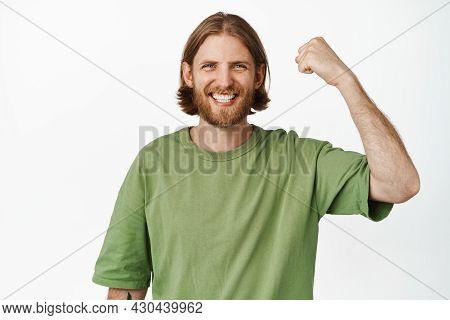 Portrait Of Excited Blond Man Chanting, Winning Something, Raising His Hand To Win, Rooting For Team
