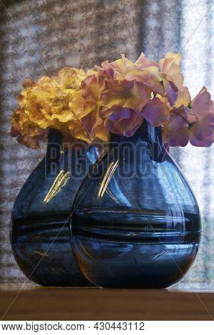 Blue Color Glass Flower Vase In Blue Blur Background
