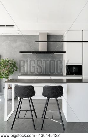 Black And White Themed Kitchen With Minimalist Design In Mind, Counter With Pair Of Bar Stools Next