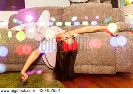 Happy Woman Concept : Beautiful Young Woman With Long Hair Lying On A Gray Sofa Listening To Music F