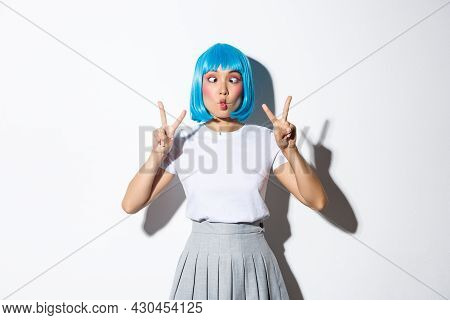 Portrait Of Silly And Cute Asian Girl In Blue Wig, Squinting And Making Funny Faces, Showing Peace G