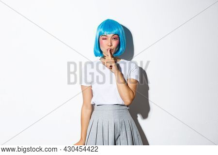 Sassy Coquettish Asian Girl In Blue Wig Have A Secret, Winking And Shushing At Camera With Sensual E