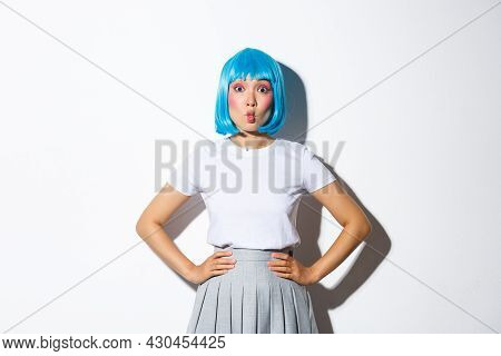 Portrait Of Beautiful Korean Girl Pouting Coquettish, Looking At Camera Silly, Standing In Blue Wig