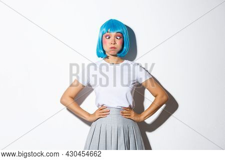Portrait Of Funny Cute Asian Girl Having Fun On Party, Pouting And Squinting, Making Grimaces And Si