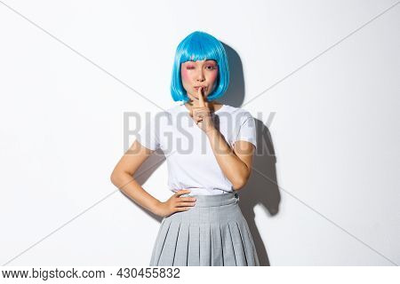 Sassy Asian Girl In Blue Wig Share A Secret, Winking And Shushing At Camera With Flirty Expression,