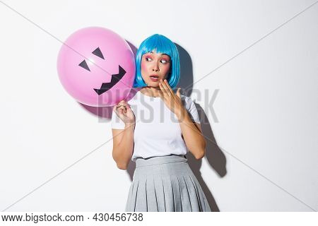 Cute And Silly Asian Girl In Blue Wig, Celebrating Halloween, Looking Surprised At Balloon With Scar