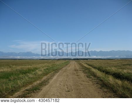 Steppe, Road And Mountains, Blue Sky. Border Of Russia And Mongolia