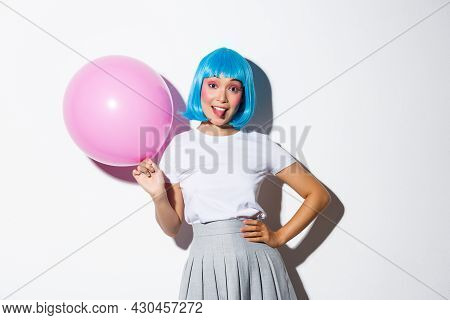 Image Of Silly Party Girl In Blue Wig Celebrating Holiday, Holding Pink Balloon And Showing Tongue,