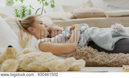 Happy Mom Cuddles Her Son Child Baby, Lying At Home Between Pillows, Healthy And Cared For Growth Co