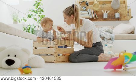 Happy And Smiling Mom With The Beautiful Baby Child Inside A Wooden Box, Eating Pop Corn Sitting At