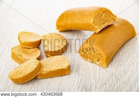Sweet Creamy Sausages With Peanut (oriental Sweets), Slices Of Sweets On Wooden Table