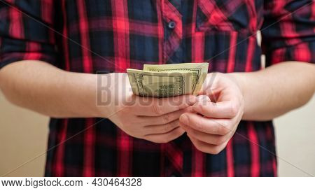 Woman In Trendy Black Red Checkered Shirt Counts Dollar Banknotes Holding In Hands And Planning Budg