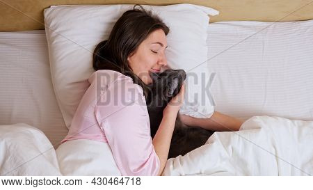 Calm Relaxed Long Dark Haired Woman In Pale Pink Pajama Lies In Queen Size Bed Near Grey Cat Side To