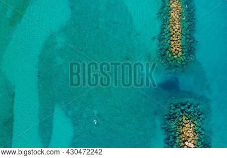 Aerial View From Flying Drone Of Crystal Blue Water And Sea Wall.