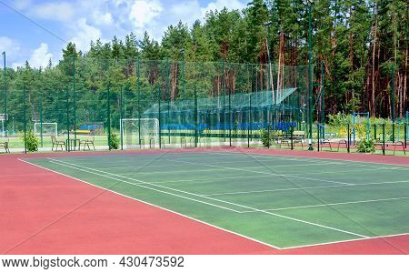 Sports Ground On The Outskirts Of The City In A Wooded Area. View Of The Tennis Court, Fitness Equip