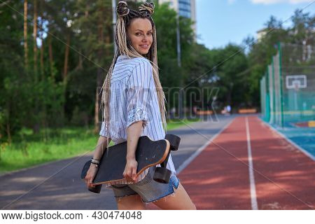 Bright Girl With Long Light Pigtails Stands With Her Back To The Camera, Holds A Longboard And Smile
