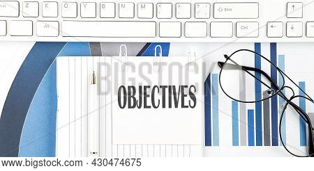 Office Desk Table With Keyboard, Chart,glasses And Pen. Top View With Objectives