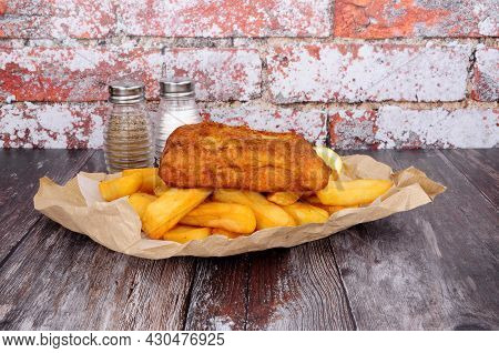 Battered Cod Fish And Chips Meal Wrapped In Brown Paper