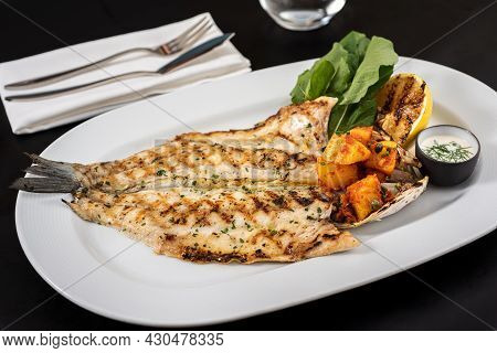 Grilled Sea Bass And Potatoes On A White Porcelain Plate.