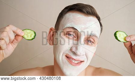 Young Man With A Mask On Face Plays With Cucumber Rings And Makes Grimaces.