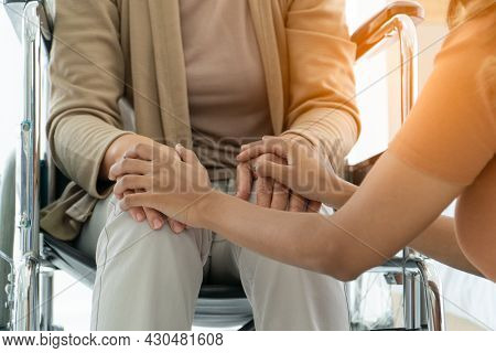 Daughter Take Care Sitting And Touch Hand Mother Elderly Caucasian Disability On Wheelchair Depresse
