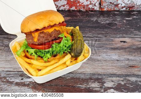 Cheeseburger And French Fries In A Take Away Box With Pickled Gherkin