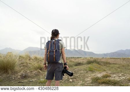 Rear View Of An Asian Photographer With Backpack Looking At View With Camera In Hand