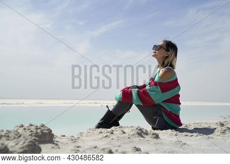 Side View Of Asian Woman Tourist Sitting By A Salt Lake Looking At View