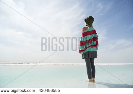 Rear View Of An Asian Woman Tourist Standing In The Middle Of A Shallow Salt Lake Looking At View