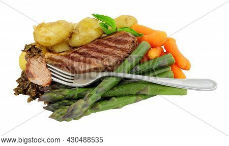Lamb Rump Steak Meal With New Potatoes, Asparagus And Carrots Isolated On A White Background
